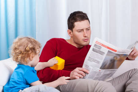 Bored child looking at father reading newspaper photo