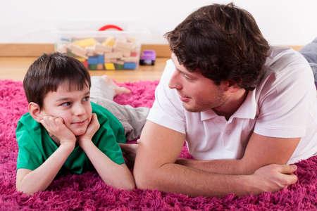 Молодой красивый папа лежал на полу со своим сыном Фото со стока