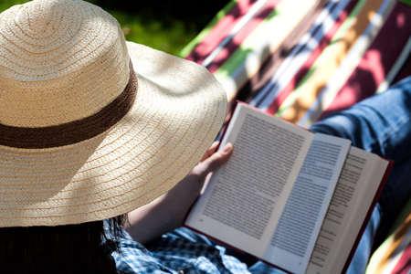 一个女人在吊床上看夏季小说