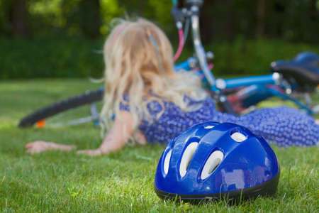 Little blond girl after fall of a bike next to blue safety helmet