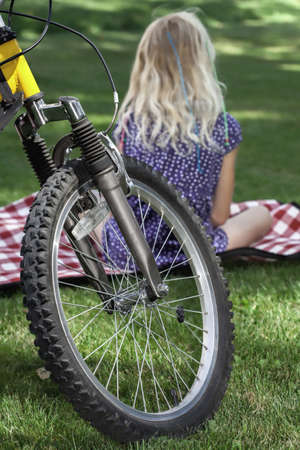 Girl on a blanket in front of her bike photo