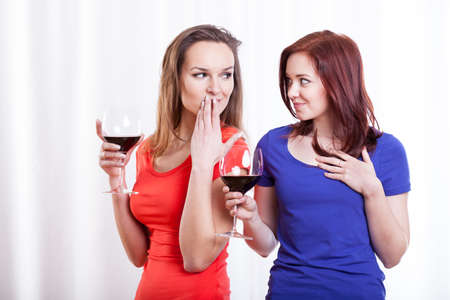 Beautiful young ladies during drinking red wine photo