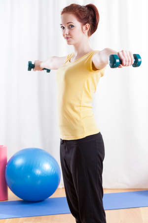 Girl practising at the fitness room, vertical photo