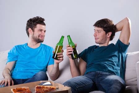 Men friends drinking beer and eating pizza photo