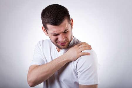 Hombre atractivo joven que tiene dolor en el hombro Foto de archivo - 27418456
