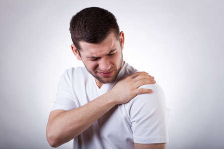 epaule douleur: Jeune homme séduisant ayant la douleur de l'épaule
