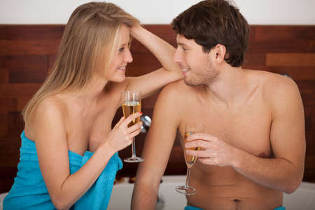 A couple proposing a toast with champagne in the bathroom photo