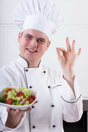 recommendation: Smiling young chef showing ok hand sign Stock Photo
