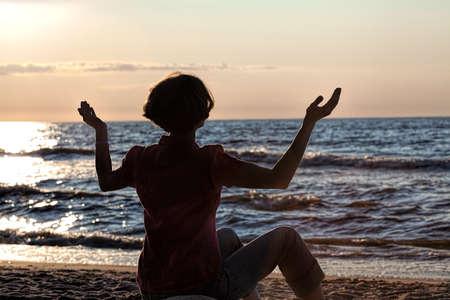 meditates: Women sitting on a beach and meditates