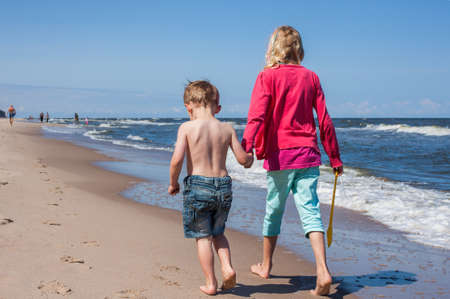 fraternal: Children walking down together along the beach holding hands
