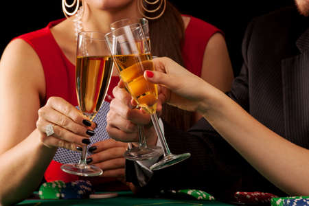Gamblers drinking a glass of champagne by a table photo