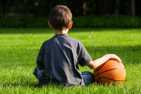 boy basketball: Ball held on a grass by sitting next to it little boy Stock Photo