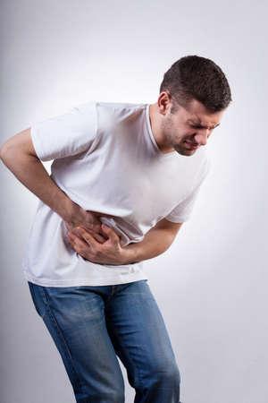 胃の痛みに苦しんでいる若い男