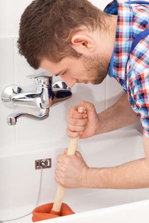 Young plumber unclogging a bathtube drain with plunger photo