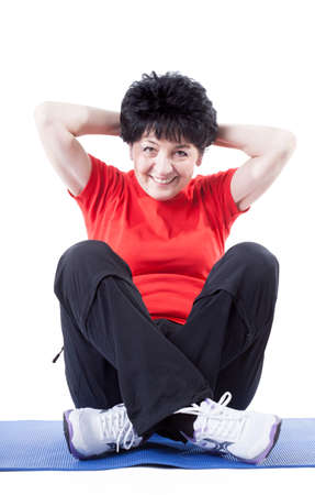 situps: A middle-aged woman in workout clothes doing sit-ups Stock Photo
