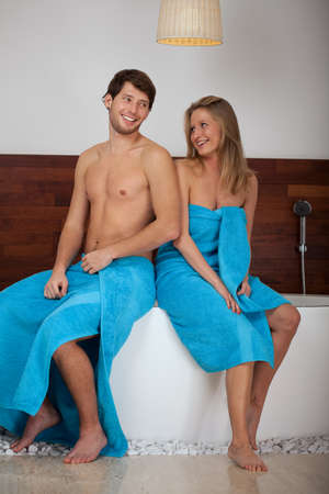 A happy couple sitting on a bath wearing towels photo