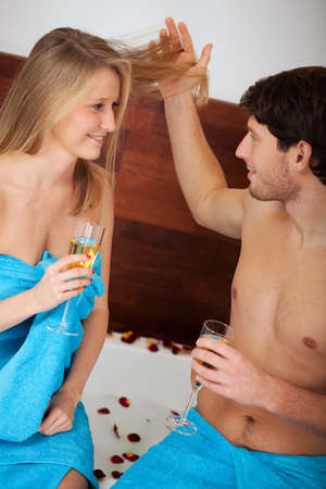 wife of bath: A husband drinking champagne and playing with his wifes hair Stock Photo