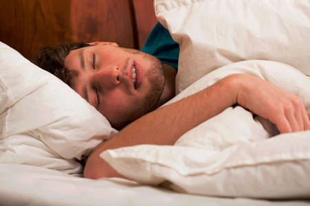 confortable: Young man sleeping peacefully in confortable bed Stock Photo