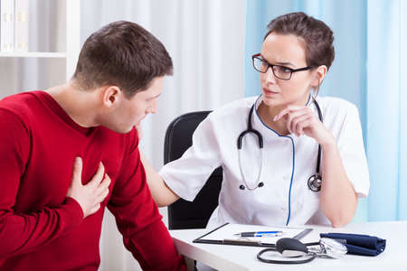 Jonge vrouwelijke arts die patiënt in het bureau onderzoekt