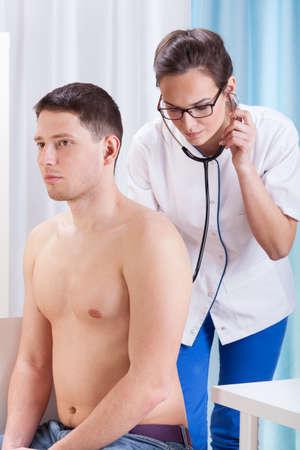 nackte brust: Ärztin untersucht Patienten mit Stethoskop im Büro