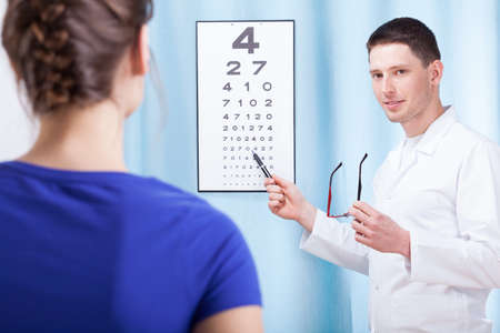Young oculist doctor examining patient with table photo