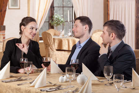 Three colleagues sitting in restaurant celebrating a project photo