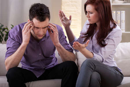 discontent: Man getting a headache in the middle of marital quarrel