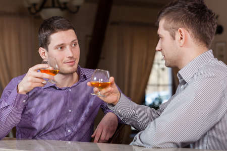 Two businessmen drinking together cognac after work photo