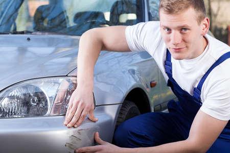 Mecánico hermoso durante la reparación del coche rayado, horizontal