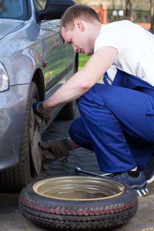 flat tyre: Young mechanic during changing flat tyre, vertical Stock Photo
