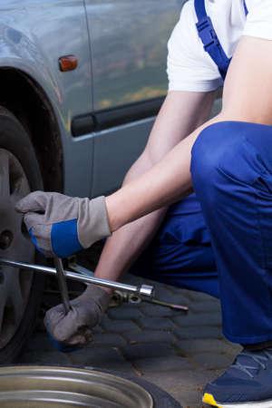 flat tyre: Handyman changing flat tyre in garage