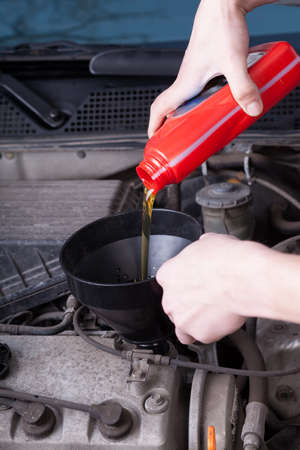 Mechanic during pouring motor oil in garage photo