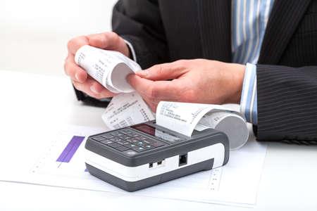 cash receipt: Businessmans hands holding long receipt from cash register Stock Photo