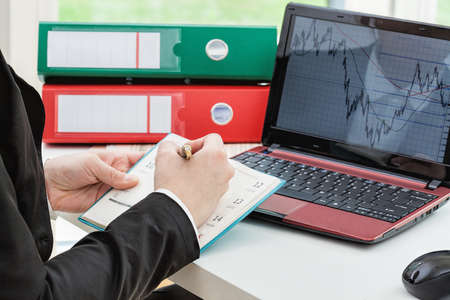 analyses: An office worker making notes based on a graph on their screen
