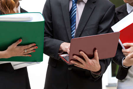 netbooks: Office workers holding file binders and netbooks