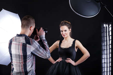 Top model in black dress posing to the photo