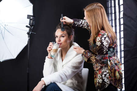 showbusiness: Model drinking coffeee and make-up artist with a brush