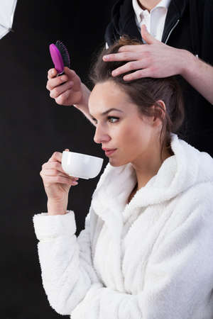 showbusiness: Actress drinking coffee in bathrobe and hairdresser making her hair