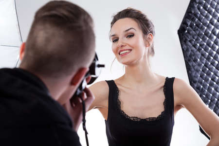 studio shoot: Model in black dress smiling for a photo