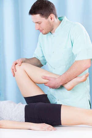 Male physiotherapist doing professional leg massage to patient photo