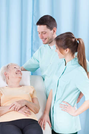 Elderly woman lying on bed talking to doctors photo