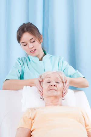 Female masseur giving head massage to elderly woman photo