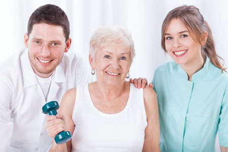 physiotherapists: Portrait of physiotherapists and exercising elderly woman Stock Photo