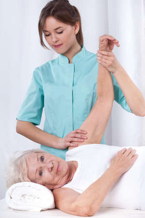 física: Los ejercicios de fisioterapia para el brazo del paciente anciano Foto de archivo