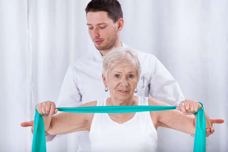 Young physiotheraqpist assisting elderly woman in exercising photo