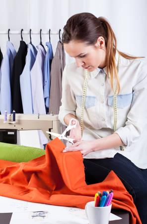 Seamstress cutting the orange fabric at studio photo