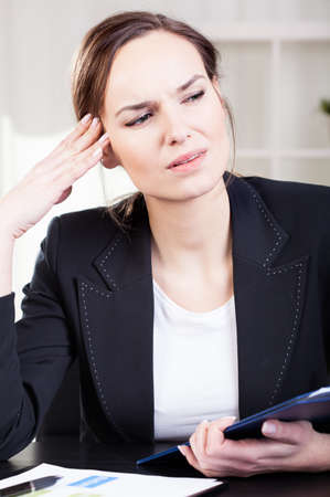 Stressed business woman getting headache at work photo
