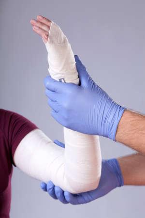 bandaged: Doctor holding bandaged arm his patient