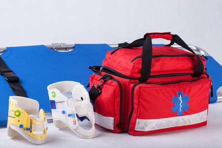 first aid kit: Bolsa de rescate, collarines cervicales y camilla en el fondo blanco Foto de archivo