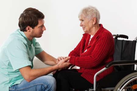 personas ayudando: Joven enfermera llena de compasión de la señora en silla de ruedas asistir